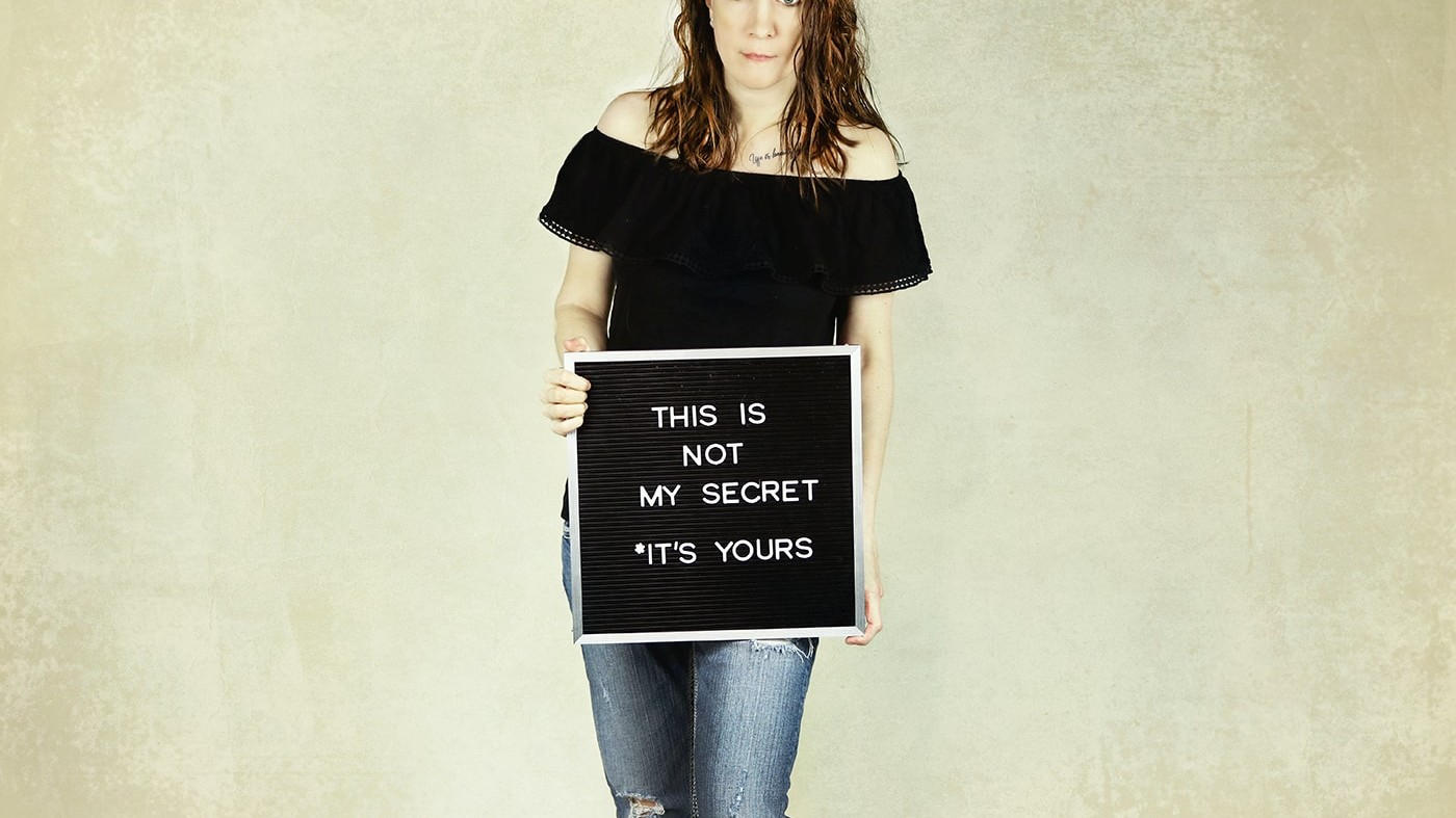 woman holding sign saying it's not my secret it's yours